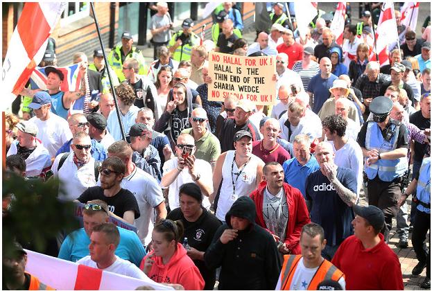 EDL marching in Nottingham featuring Ian kellett *Sunglasses and Union Jack scarf), Craig Burridge (white vest, cap, lanyard), Jack Stevens (black coat, hood up) and Daniel Hall (red shirt, black cap)